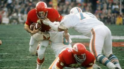 Ed Podolak is tackled by Dophins LB Nick Buoniconti and DT Manny Fernandez.