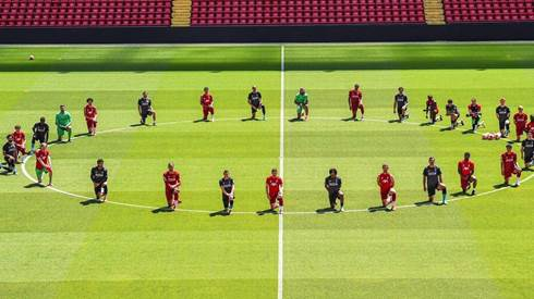 Liverpool players kneel down at Anfield in tribute to George Floyd